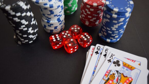 Poker chips and playing cards scattered on a table.