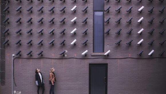 Two people on the street being watched by dozens of CCTV cameras.