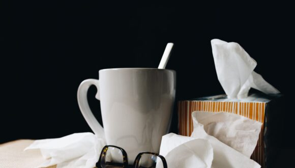 Mug of tea, glasses, box of tissues and excess tissues on a table.